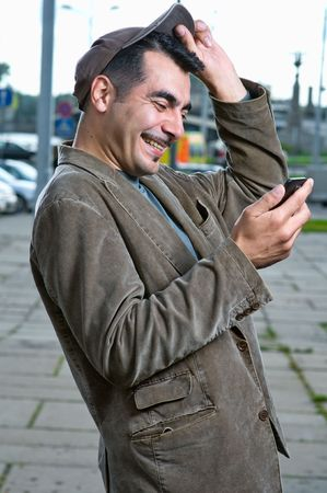 Happy handsome man with mobile phone outdoors  photo