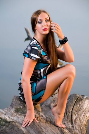 Romantic young brunette with long hair relaxing outdoors photo