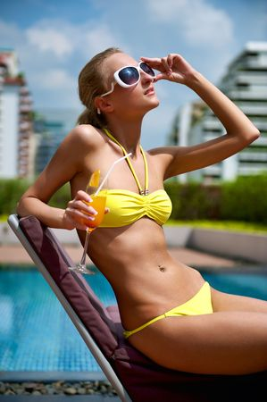 deckchair: Beautiful young woman drinking cocktail near a swimming pool