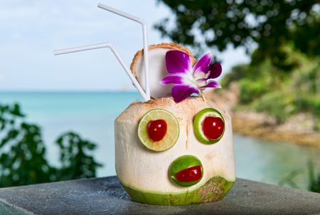 lakefront: Exotic coconut cocktail against blue water and sky