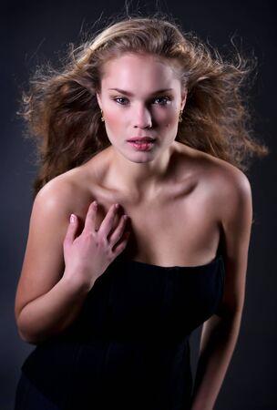 Elegant beautiful woman in fashion  dress posing isolated on black Stock Photo - 8337871