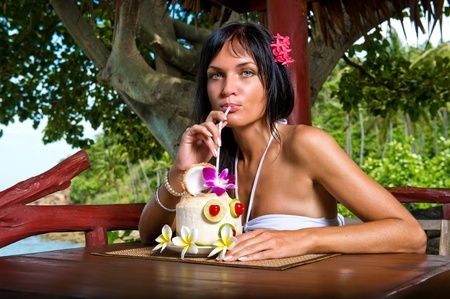Beautiful young woman drinking cocktail outdoors photo