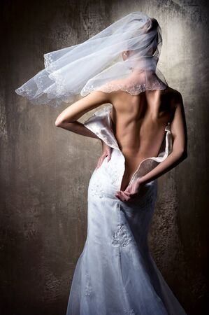 Lovely sensual bride unzip her wedding dress photo