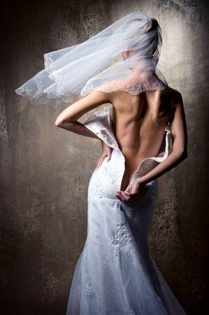 Lovely sensual bride unzip her wedding dress photo