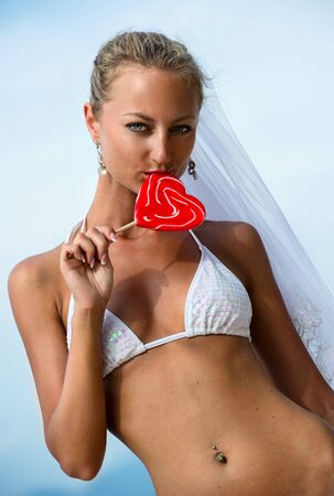 Beautiful girl holding a lollipop on the beach Stock Photo - 8572741