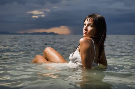 Beautiful brunette posing in a water at sunset Stock Photo