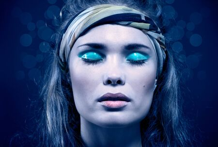 Beautiful young woman with blue make-up. Isolated on blue photo