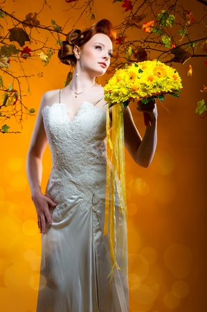 Beautiful redhead bride with a bouquet of flowers photo