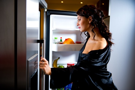 Young woman looking for something to eat inside the fridge Stock Photo - 8975293