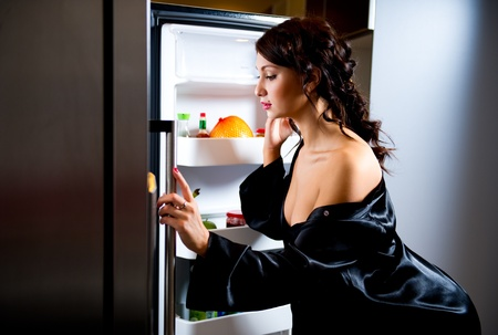 Young woman looking for something to eat inside the fridge photo