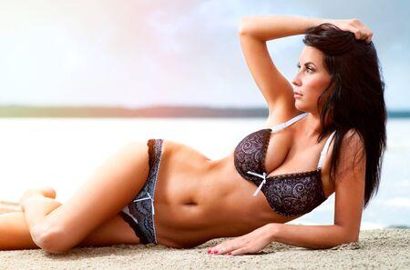 beaux seins: Belle jeune femme relaxante sur la plage.