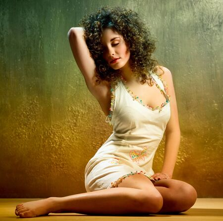 poses de modelos: Encantadora joven mujer con cabello rizado en interiores Foto de archivo