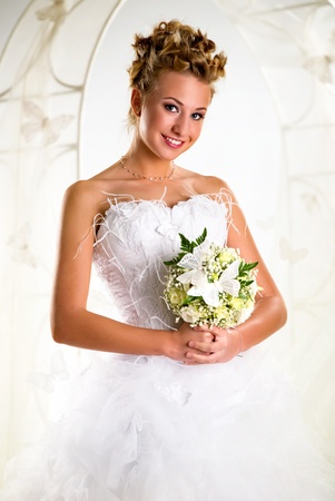 Beautiful bride with bouquet of flowers over summer background Stock Photo