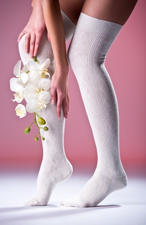 Beautiful woman legs in cotton stockings and  white orchid photo