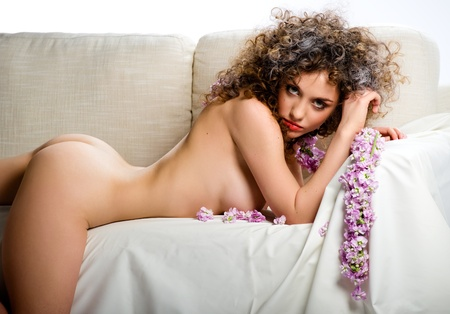 Naked young woman lying on a couch