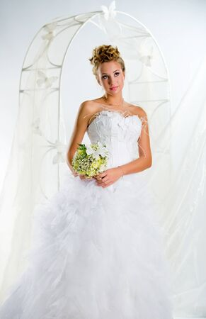 Beautiful bride with bouquet of flowers indoors photo