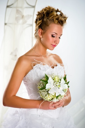 Lovely bride with bouquet of flowers close-up portrait photo