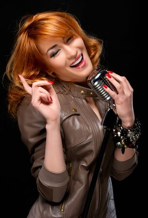 Portrait of a beautiful redhead singer over black background photo
