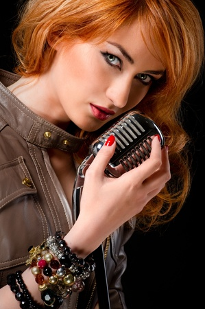 Beautiful redhead girl with microphone photo