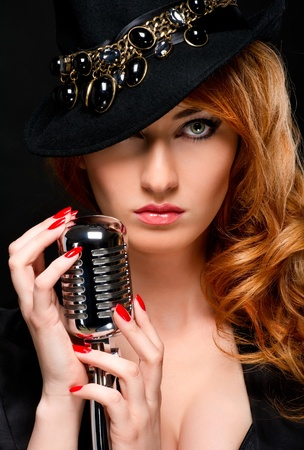 Beautiful redhead girl with retro microphone photo