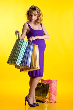 Beautiful pregnant woman looking inside shopping bags  photo
