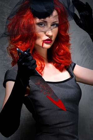 Redhead woman with blood on her lips and bloody knife in hand photo