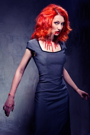 Portrait of a redhead woman with blood in her lips and neck indoors photo