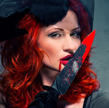 Gorgeous redhead woman with bloody knife in her hand close-up Stock Photo - 9698417