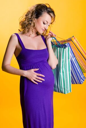 Lovely pregnant woman holding shopping bags isolated on yellow background Stock Photo - 9698466