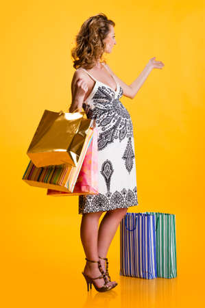 Lovely pregnant woman with shopping bags gesturing indoors photo
