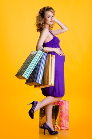 Beautiful pregnant woman holding shopping bags isolated on yellow background Stock Photo - 9698468