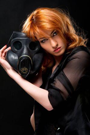Redhead woman holding gas mask photo