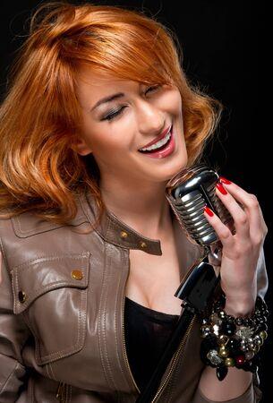 Beautiful redhead young woman singing photo