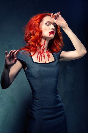 Redhead woman with blood in her face and neck  photo