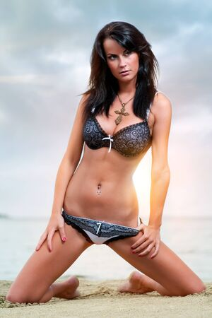 Beautiful young brunette relaxing on the beach photo