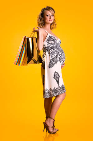 Lovely pregnant woman holding shopping bags isolated on yellow background photo