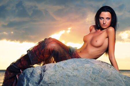 beach breast: Beautiful young woman relaxing on the beach near the sea