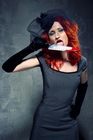 woman knife: Gorgeous redhead woman with bloody knife in her hand   Stock Photo
