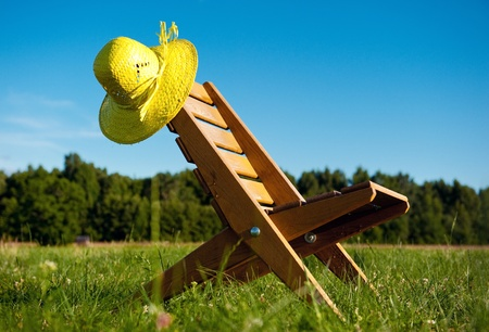 straw hat: Armchair and straw hat outdoors Stock Photo
