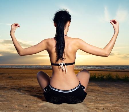 Woman doing yoga exercise outdoors photo