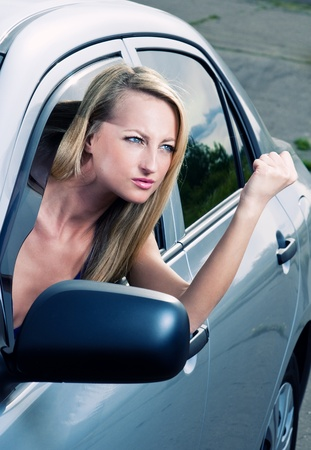 Angry blond young woman sitting in a car photo