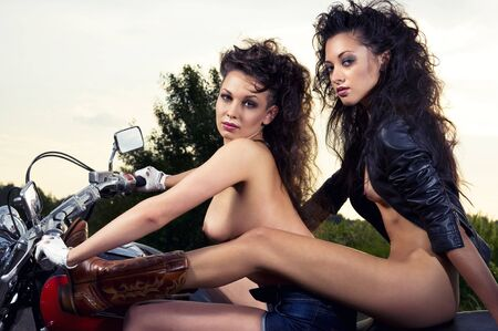 Two sexy young woman sitting on a motorcycle outdoors Stock Photo - 10355757