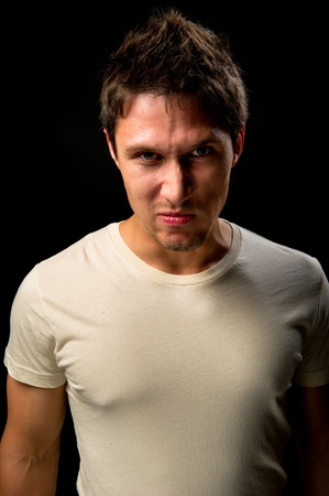 Portrait of a handsome angry man over black background  photo