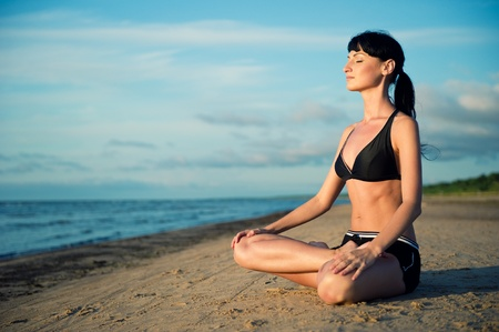 Woman doing yoga exercise outdoors Imagens