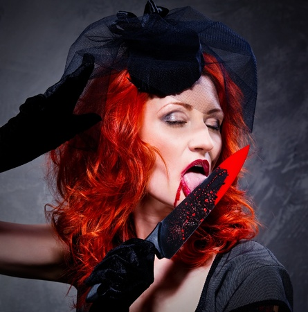 Gorgeous redhead woman with bloody knife in her hand close-up photo
