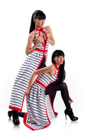 Beautiful stylish twin sisters posing over white background  photo