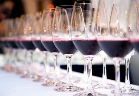 weinverkostung: Gl�ser Rotwein in einer Reihe auf einem Tisch Lizenzfreie Bilder
