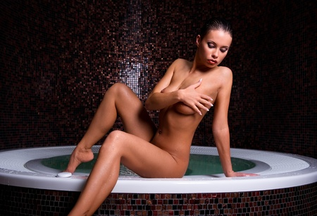 Attractive naked woman relaxing in jacuzzi  Stock Photo