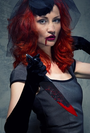 woman knife: Redhead woman with blood on her lips and bloody knife in hand