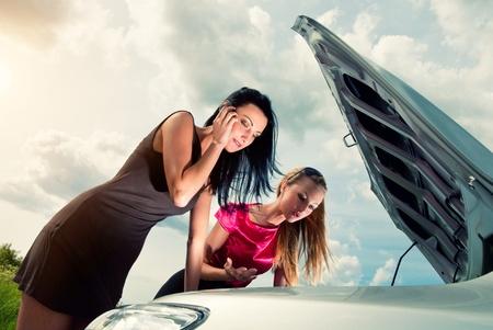 Twee jonge vrouwen met kapotte auto op een weg